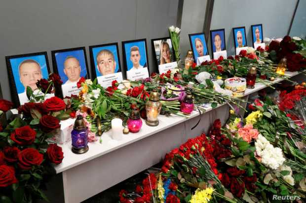 Flowers and candles are placed in front of the portraits of the flight crew members of the Ukraine International Airlines Boeing 737-800plane that crashed in Iran, at a memorial at Boryspil International airport outside Kiev